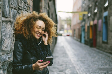 Ireland, Dublin, smiling woman with afro hearing music with smartphone and earphones - BOYF000035