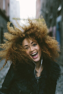 Portrait of happy woman with afro hearing music with earphones - BOYF000038