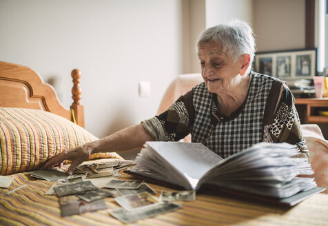 Senior woman adding old photos to a photo album at home - RAEF000692