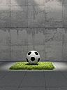 Soccer ball lying on lawn square in front of concrete wall, 3D Rendering - UWF000700