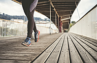 Spain, Naron, legs of a jogger running on a wooden bridge - RAEF000696
