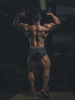 Bodybuilder pperfroming a back double biceps pose in gym - MADF000765