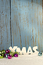 Christmas decoration with baubles and artificial snow in front of wooden wall - LBF001305