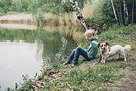 Germany, Saxony, boy with dog at the lakeside - MJF001704