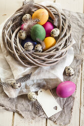 Colourful Easter eggs and quail eggs in rustic nest - SBDF002547