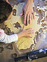 Mother and little daughter cutting out Christmas cookies, close-up - KRPF001659