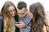 Three friends looking at cell phone together - MGOF001142