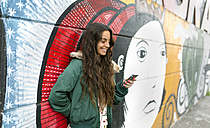 Smiling young woman looking at cell phone at mural - MGO001148