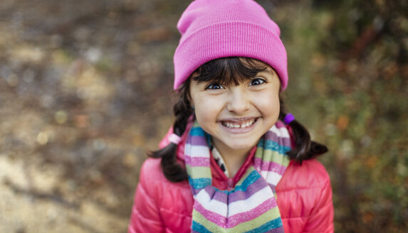 Portrait of grinning little girl wearing cap and scarf in autumn - MGOF001155