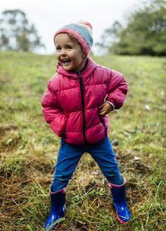Portrait of laughing little girl standing on a meadow in autumn - MGOF001158