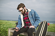 Young casual man sitting in a park with his longboard, he is looking his smartphone - RAEF000711
