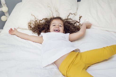 Laughing little girl lying on bed - LITF000095