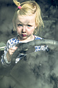 Portrait of blond toddler sitting behind steering wheel in a car - GSF001043