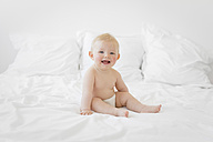 Portrait of smiling blond baby boy only wearing diaper sitting on a bed - LITF000128