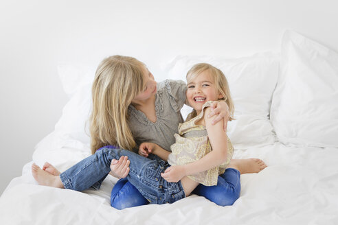 Big sister holding little sister in her arms on a bed - LITF000131