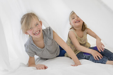 Two laughing little sisters hiding under a white sheet on a bed - LITF000134