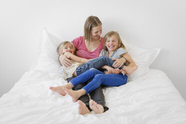 Mother lying with her laughing little daughters on the bed - LITF000137