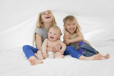 Portrait of three laughing siblings sitting on a bed hiding under white sheet - LITF000143