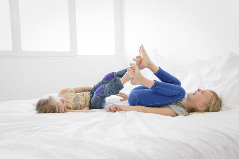 Two little sisters lying on bed playfighting with their feet - LITF000149