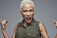 Portrait of screaming woman in front of grey background - RHF001082