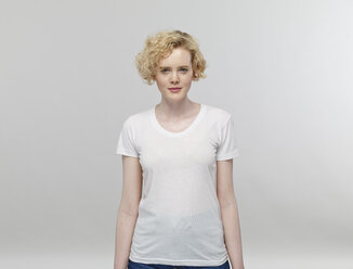 Portrait of blond woman wearing white t-shirt in front of grey background - RHF001085