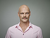 Portrait of bald man with moustache wearing pink shirt - RHF001121