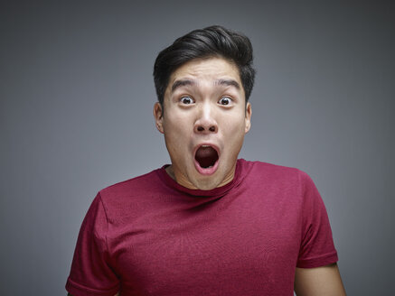 Portrait of shocked young man in front of grey background - RHF001130