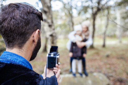 Father taking picture of wife and daughter in the forest - MGOF001165