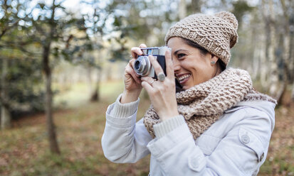 Happy woman taking a picture in the forest - MGOF001171