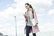 Young woman with earbuds and cell phone on the go - UUF006169