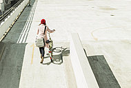 Young woman pushing bicycle on parking level - UUF006175