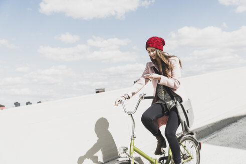Young woman on bicycle looking at cell phone - UUF006178
