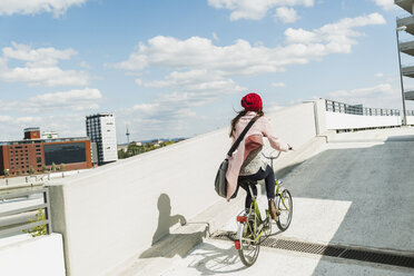 Young woman riding bicycle on parking level - UUF006181