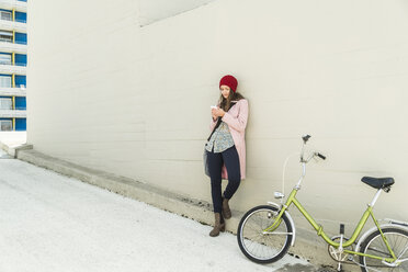 Young woman next to bicycle looking at cell phone - UUF006187