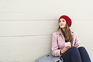 Young woman sitting at concrete wall holding cell phone - UUF006190