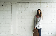 Young woman at brick wall holding satchel bag - UUF006193