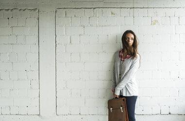 Young woman at brick wall holding satchel bag - UUF006193
