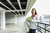 Young woman with cell phone in parking garage - UUF006196