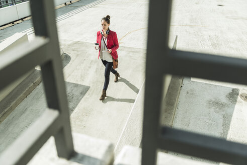 Young woman with coffee to go, headphones and phablet walking on parking level - UUF006202