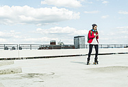 Young woman with cell phone and inline skates on parking level - UUF006205
