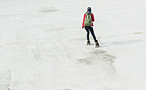 Young woman with backpack inline skating on parking level - UUF006208