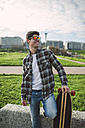 Smiling young man with longboard wearing mirrored  sunglasses - RAEF000720