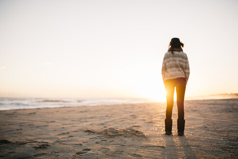 Back view of young woman standing on the beach in winter - JRFF000242