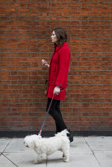 Young woman wearing red jacket going walkies with her dog - MAUF000146
