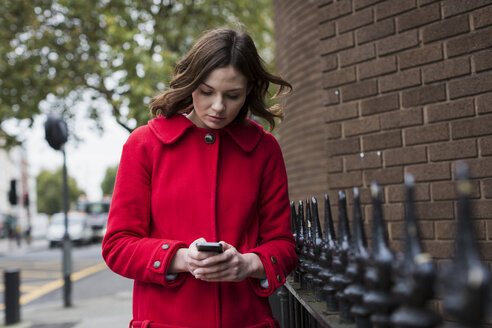 Young woman wearing red jacket looking at her smartphone - MAUF000155