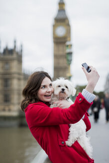 UK, London, portrait of smiling young woman with dog on her arm taking a selfie with smartphone - MAUF000158