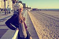 Spain, Cadiz, El Puerto de Santa Maria, woman with winter clothes looking at beach - KIJF000039