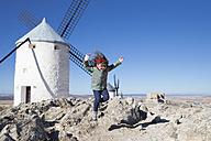 Spain, Consuegra, jumping little girl with windmill in the background - ERLF000091