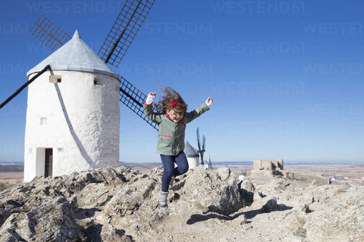 Spain, Consuegra, jumping little girl with windmill in the background - ERLF000091 - Enrique Ramos/Westend61