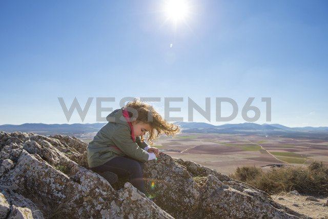 Spain, Consuegra, little girl sitting on a rock of a mountain - ERLF000094